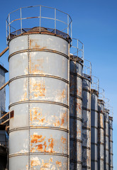 Rusted gray tall tanks on old factory