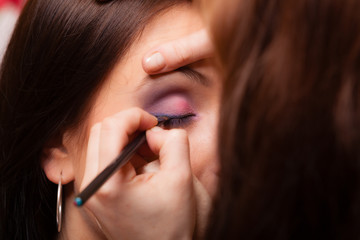 Makeup artist applying with brush eyeshadow on eyelid of woman