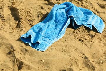 closeup of blue towel on a sandy beach. Relax.