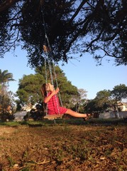 Happy child swinging in outdoor playground