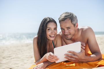 handsome couple on the seaside lying on a beach towel to use a d