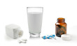 pill bottle and glass of milk isolated on white background