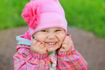 Funny laughing Caucasian baby girl in pink