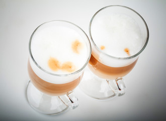 Two glasses of latte coffee with milk foam