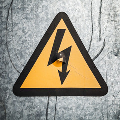 High voltage triangle sign mounted on gray metal wall