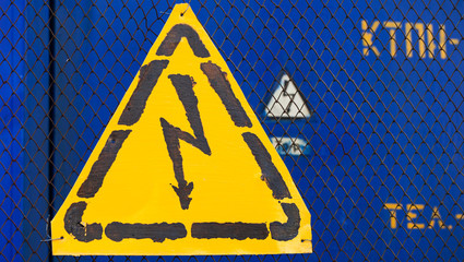 High voltage yellow sign mounted on blue metal rabitz grid with