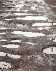 Rural dirty damaged road with muds and holes