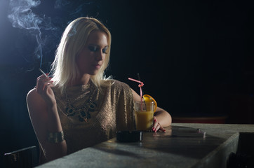 Beautiful elegant lady sitting alone in the night club and smoki