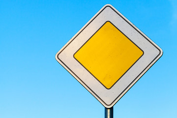 Main road yellow roadsign above clear blue sky background