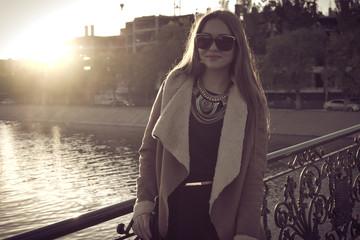 Sepia toned retro portrait of a beautiful girl in sunglasses