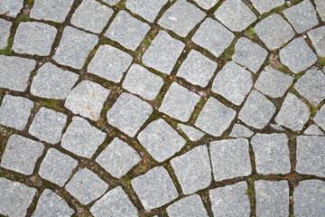Gray granite cobblestone pavement. Closeup background texture