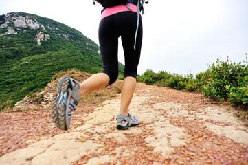 young fitness woman hiker legs walking on seaside mountain trail