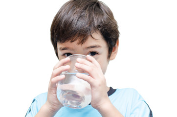little boy drinks water from a glass