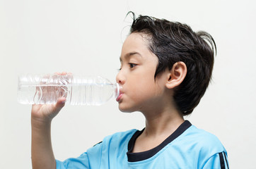 little boy drinks water from a bottle after excercise