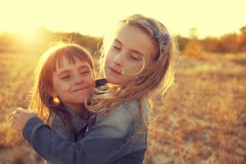 two girls running around the sunny field