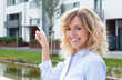 Frau mit blonden Locken zeigt ihre Traumwohnung - 71464513