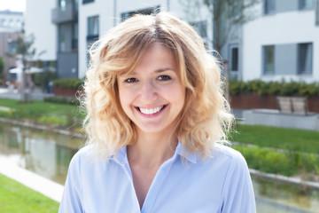 Lachende Frau mit blonden Locken im Wohngebiet