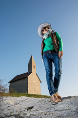 Posing young woman in a stylish hat and an old romanesque church