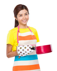 Asian housewife holding of saucepan with gloves