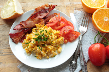 Breakfast with scrambled eggs with bacon and fresh tomatoes