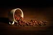 tazzina con chicchi di caffè rovesciati