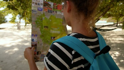 Girl Wearing Backpack Holding Map on the Beach.