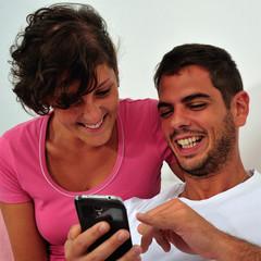 Couple sitting looking smartphone