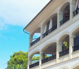 Part of modern luxury hotel against blue sky.
