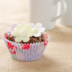 Home made cupcake on a rustic hessian background