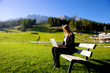 Blond business woman working in front of mountain italian alps