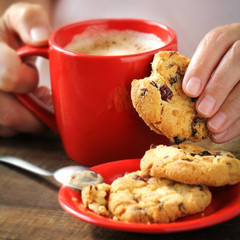 Female hands holding red cup cup of cappuccino and cookie