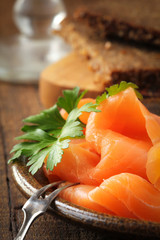 Slices of smoked salmon with a fresh leaf of parsley