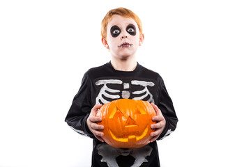 Red haired boy in skeleton costume holding a pumpkin. Halloween