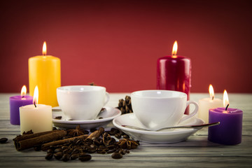 Fir-tree cones of a candle with cups for coffee on an old backgr