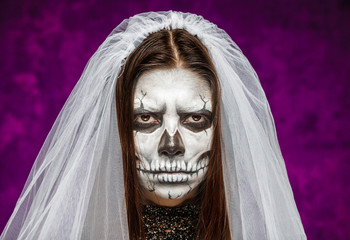 Young woman a bride in a veil on the day of the dead mask skull