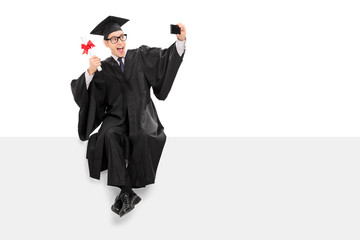 College graduate taking selfie seated on a panel
