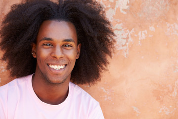 Portrait Of Smiling Man Leaning Against Wall