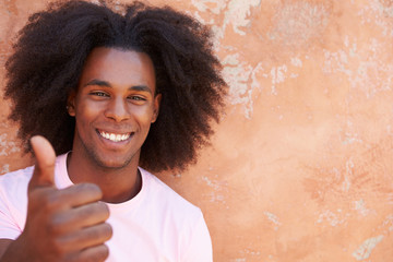 Smiling Man Leaning Against Wall Giving Thumbs Up