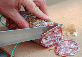 Cook's hand slicing the salami