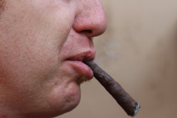 smoker with long Cuban cigar in his mouth