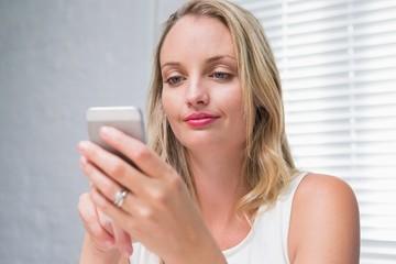 Beautiful businesswoman text messaging