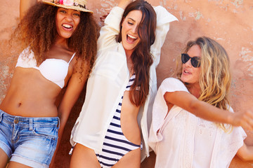 Group Of Female Friends On Holiday Together Posing By Wall