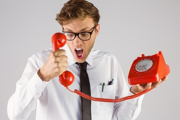 Angry geeky businessman holding telephone