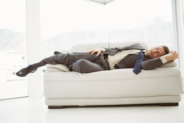Businessman sleeping on couch in living room