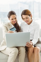 Happy young businesswomen doing online shopping