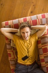 Young man listening to music on his couch