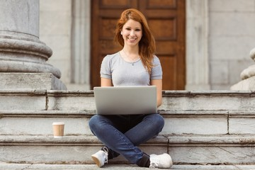 Smiling woman with disposable cup using laptop