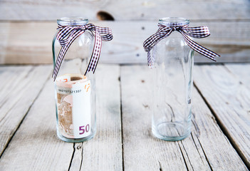 Money in a glass jar and an empty jar