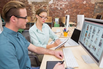 Casual photo editors using computer in office