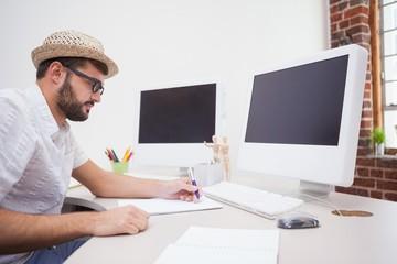 Casual designer drawing at his desk